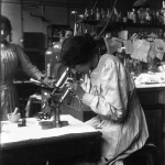 A Paris : le laboratoire municipal, femme regardant au microscope, 1915