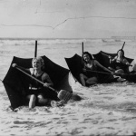 Sur une plage de Floride, jeunes filles se faisant porter par leur parapluie renversé formant un bateau et se servant d'un balai comme rame, 1932