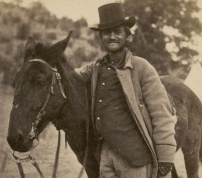 Fred. W. Loring, in his campaign costume, with his mule Evil Merodach. / Timothy O'Sullivan, 1871<br>============================